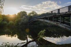 Paisaje con puesta del sol Puente sobre el río Imagen de archivo
