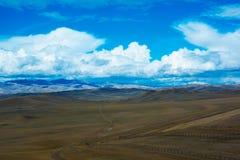Paisaje con un camino, montañas, cielo azul de la estepa fotografía de archivo