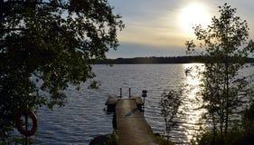Paisaje con un embarcadero y un lago Imagen de archivo libre de regalías