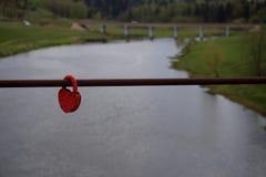 Paisaje con una cerradura roja del granero encadenada a una cerca de un puente sobre el río imagenes de archivo