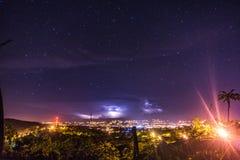 Paisaje con vista a los ligths de la ciudad de la tormenta eléctrica en el nigth estrellado fotos de archivo libres de regalías
