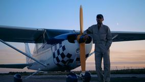 Paisaje crepuscular con un aviador de sexo masculino que se coloca al lado de un cropduster almacen de video
