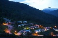 paisaje crepuscular del pueblo en la colina con la luz multicolora hermosa imagenes de archivo