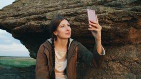 Paisaje de fotografía del backpacker turístico joven de la mujer en su cámara del smartphone después de caminar en roca en la pue Imagenes de archivo