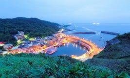 Paisaje de la carretera costera que cruza el puerto de un pueblo pesquero con las luces de los barcos de pesca en el mar ~ Imágenes de archivo libres de regalías