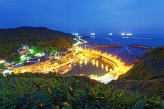 Paisaje de la carretera costera que cruza el puerto de un pueblo pesquero con las luces de los barcos de pesca en el mar imagen de archivo libre de regalías