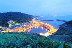 Paisaje de la carretera costera que cruza el puerto de un pueblo pesquero con las luces de los barcos de pesca en el mar ~ Imagen de archivo