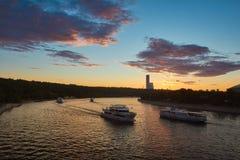 Paisaje de la ciudad en la puesta del sol con un río en el primero plano Foto de archivo libre de regalías