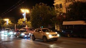 Paisaje de la ciudad de la noche con los coches en el camino y las banderas almacen de video