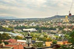 Paisaje de la ciudad de Tbilisi con las señales famosas Puente de la paz, de la sala de exposiciones y de la trinidad santa Sameb fotos de archivo libres de regalías