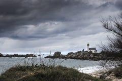 Paisaje de la costa costa en marea baja con el faro y el rocho peculiar Imagen de archivo libre de regalías