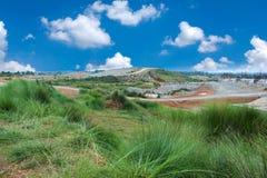 Paisaje de la hierba verde y de las peque?as colinas con el cielo de la nube fotografía de archivo