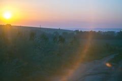 Paisaje de la mañana Salida del sol detrás del pueblo en el campo Imagen de archivo libre de regalías