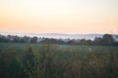 Paisaje de la mañana Salida del sol detrás del pueblo en el campo Fotografía de archivo
