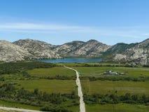 Paisaje de la montaña con el camino y el lago Fotografía de archivo