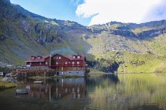 Paisaje de la montaña con la casa del lago, en la mucha altitud Fotos de archivo