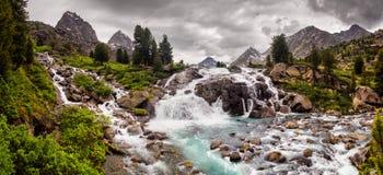 Paisaje de la montaña con la cascada y los picos Fotografía de archivo libre de regalías