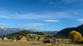 Paisaje de la montaña con las casas locales tradicionales en otoño en la puesta del sol con el cielo azul y los árboles maravillo Foto de archivo