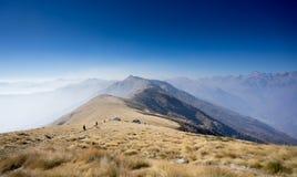 Paisaje de la montaña con los caminantes en el sendero Foto de archivo