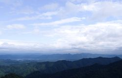 Paisaje de la montaña, con los picos de montaña cubiertos con el bosque y un cielo nublado imagen de archivo