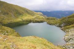 Paisaje de la montaña de la mucha altitud de un lago rodeado por las colinas verdes Foto de archivo
