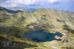 Paisaje de la montaña de la mucha altitud de un lago rodeado por las piedras Imagen de archivo libre de regalías