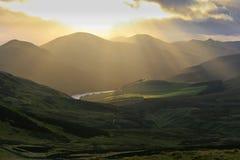 Paisaje de la montaña de las colinas de Pentland cerca de Edimburgo, con los rayos solares reflejando en un lago Fotos de archivo libres de regalías