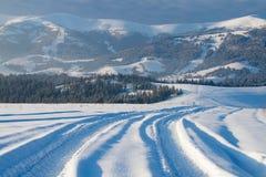 Paisaje de la montaña del invierno con el camino de la pista Foto de archivo libre de regalías