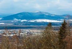 Paisaje de la montaña del invierno con el campo, la arboleda y el pueblo adentro lejos Imagen de archivo