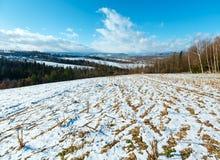 Paisaje de la montaña del invierno con el campo, la arboleda y el pueblo adentro lejos Imágenes de archivo libres de regalías