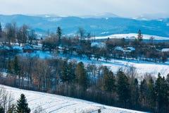 Paisaje de la montaña del invierno con el campo, la arboleda y el pueblo adentro lejos fotografía de archivo libre de regalías