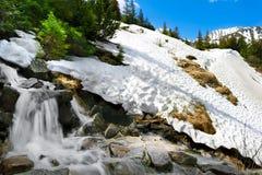 Paisaje de la montaña del resorte con nieve y la cascada Imagenes de archivo