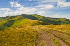 Paisaje de la montaña del verano con el camino y la sombra de nubes imagen de archivo