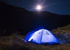 Paisaje de la montaña de la noche con la tienda azul iluminada Picos de montaña y la luna al aire libre en el lago Lacul Balea, T fotos de archivo