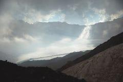 Paisaje de la montaña de una cuesta de alta montaña con una cuesta volcánica fangosa del glaciar agrietado contra el contexto del imagenes de archivo