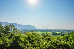 Paisaje de la naturaleza con el bosque verde, la montaña y el sol en el cielo azul, Tailandia Foto de archivo