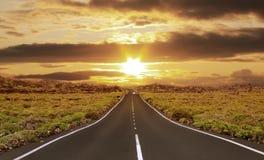 Paisaje de la naturaleza de la luz de la puesta del sol sobre la carretera de asfalto Imagen de archivo libre de regalías