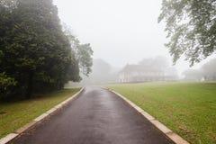 Paisaje de la niebla de la casa de la calzada Imagen de archivo libre de regalías