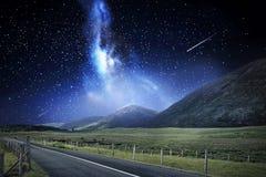Paisaje de la noche del camino y de montañas sobre espacio Imagenes de archivo