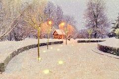 Paisaje de la noche del invierno con la casa sola iluminada bajo opinión descendente del paisaje del invierno de la nieve Foto de archivo