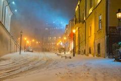 Paisaje de la noche del invierno, igualando en la calle nevosa de la noche bajo nevadas Imágenes de archivo libres de regalías