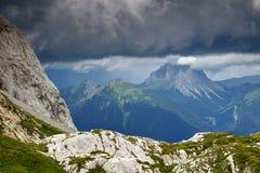 Paisaje de la piedra caliza debajo de las nubes oscuras en las montañas de Carnic, Italia Fotos de archivo