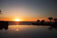Paisaje de la piscina y de la cascada en la puesta del sol Fotos de archivo