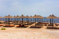 Paisaje de la playa con las camas de madera del sol, paraguas cubiertos con paja y Imágenes de archivo libres de regalías
