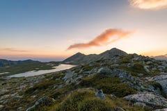 Paisaje de la puesta del sol con el pico de Kamenitsa y el lago Tevno Foto de archivo libre de regalías