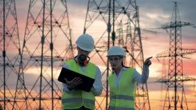 Paisaje de la puesta del sol con las líneas eléctricas y dos especialistas que hablan cerca de ellos almacen de metraje de vídeo