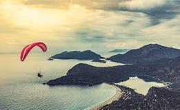Paisaje de la puesta del sol con paragliding en el cielo Vuelo en tándem del ala flexible sobre el mar Mediterráneo Playa de Olud imagenes de archivo