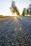 Paisaje de la puesta del sol con una carretera de asfalto rural Foto de archivo libre de regalías
