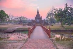 Paisaje de la puesta del sol de Wat Sa Si en el parque histórico de Sukhothai con el sol poniente en fondo, un puente de madera e Imagenes de archivo