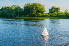 Paisaje de la puesta del sol del agua del verano - los árboles a lo largo del banco del río y de la boya en el agua bajo puesta d Fotografía de archivo libre de regalías